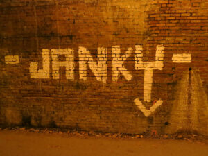"""a brick wall that has """"JANKY"""" painted on it"""