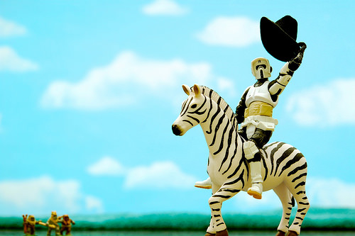 a storm trooper toy riding a zebra as he lifts a cowboy hat up in the air