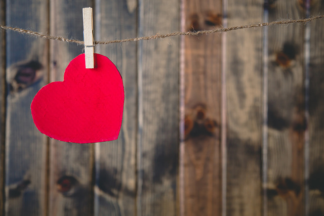 a red heart hanging from a clothespin on a clothesline in front of a wooden fence