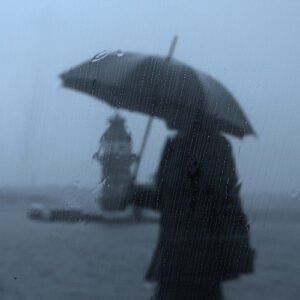 a rainy scene of a person walking with an umbrella