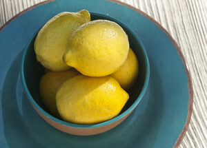 teal bowl and saucer filled with lemons