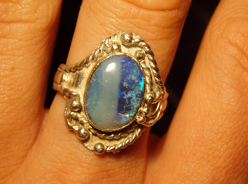 a closeup of an opal ring on a finger