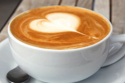 a cup of coffee with a heart-shaped spot of cream