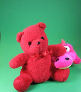 red teddy bear, pink plushie, green background