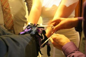 man and woman being tied together by ribbons in a polyamorous wedding ceremony
