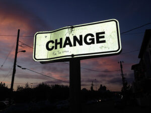 """a sign that syas """"CHANGE"""" that someone has written """"For The Better"""" on"""