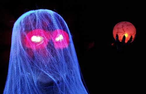a blue ghost with pink glowing eyes holding an orange orb