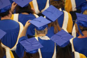 view of many graduates dressed in blue, from behind