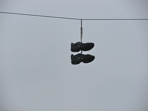 black and white photo of 2 sneakers hanging from a power line