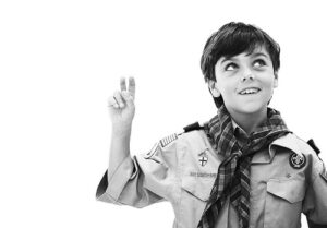 poly honor student, black and white photo of a young boy scout holding up two fingers like a peace sign
