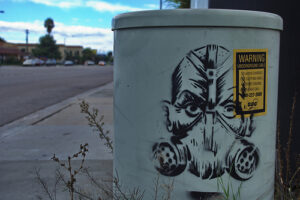 a cannister with the image of a man wearing a gas mask spray painted onto it