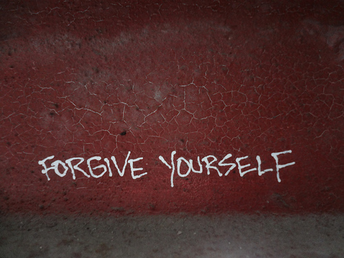 red brick wall with words forgive yourself spray painted on it in white