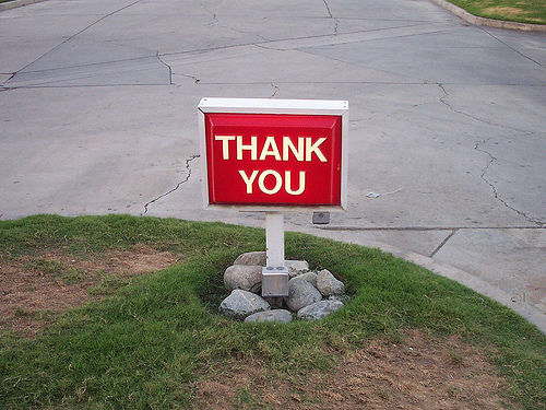 a red thank you sign on a lawn