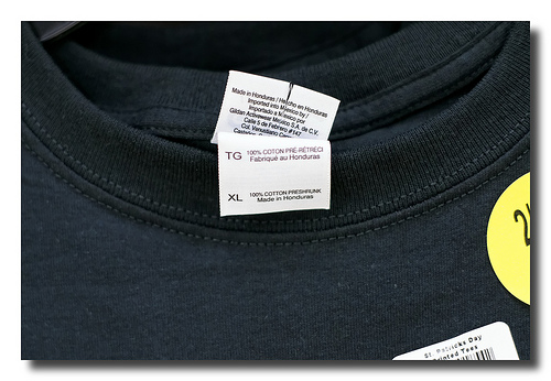 navy blue t-shirt close up with a tag sticking out that says the shirt was made in Honduras