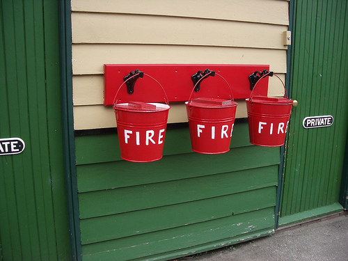 "3 red buckets hanging on a wall, each bucket says ""fire"" on it"