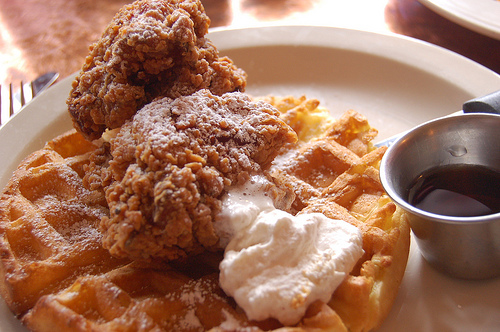 chicken and waffles with syrup and butter on a dinner plate