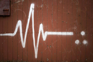 the shape of a heart pulse on an EKG spray painted with white paint onto a brick red wall