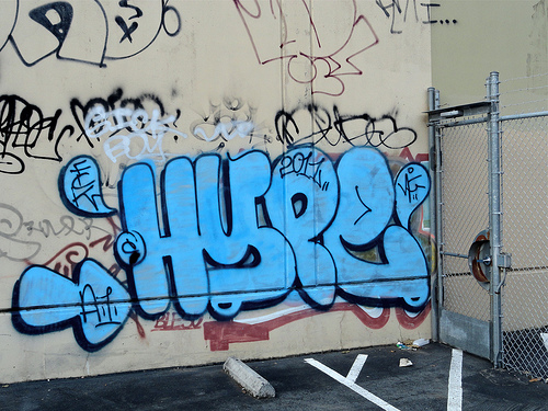 "large balloon letters of blue graffiti paint that read ""hype"" on a gray wall of a building"