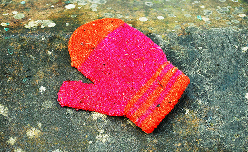 a single neon pink and orange mitten on a rock