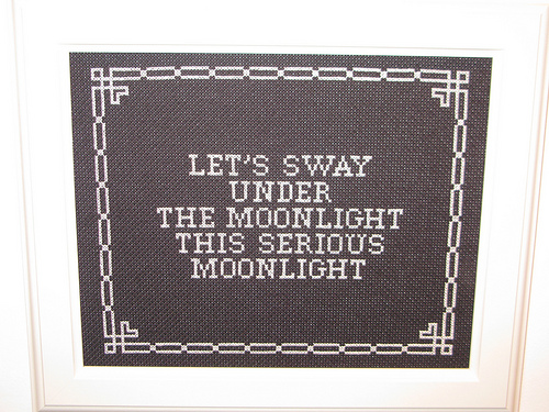 "a needlepoint sampler with the words ""let's sway under the moonlight the serious moonlight"" stitched from it (lyrics from David Bowie's song ""Let's Dance"")"
