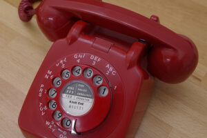 a red telephone, one with a dial