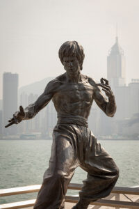 statue of Bruce Lee in Hong Kong with a city skyline faintly behind it