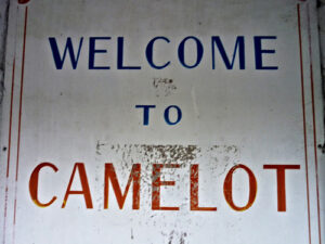 """a weathered sign that reads """"welcome to Camelot,"""" the land of King Arthur"""