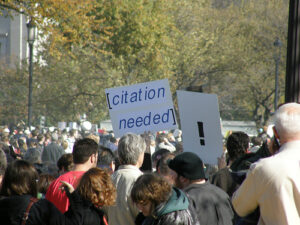 """a group of protestors, one is holding a sign that says """"[citation needed]"""""""
