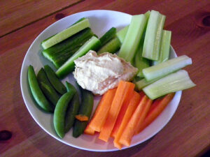 a crudite platter of celery, carrots, snow peas, and ranch dressing