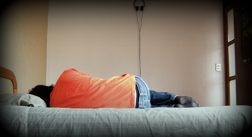 a person in an orange t-shirt and jeans lying on a bed, viewed from behind
