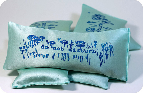 "a stack of small teal silk pillows. the top one reads ""do not disturb"" with flowers stamped next to it"