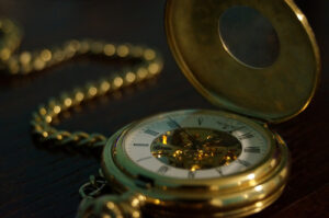 a close up of an opened gold pocket watch on a chain
