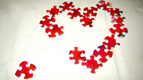 a bunch of red jigsaw puzzle pieces in the shape of a heart, with one piece missing. this missing piece is off to the side.