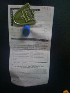 a speeding ticket from the state of Tennessee, tacked up on a black background with a blue push pin