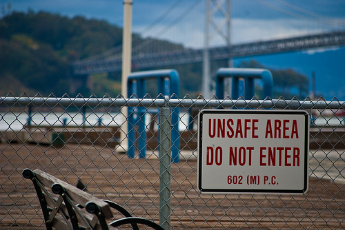"a chain link fence with a sign hanging on it that says ""unsafe area, do not enter"""