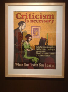 """a vintage motivational poster that reads """"Criticism is necessary. Helpful constructive criticism brings progress. Give it and take it cheerfully. When you listen you learn."""" The image on the poster is a woman seated at a desk with a man standing behind her."""