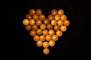 a collection of lit candles arranged in the shape of a heart, viewed from above