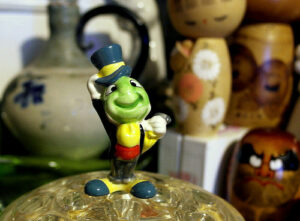 a small figurine of Jiminy Cricket, a main character of the movie Pinocchio. Jiminy Cricket is a small cricket in dress clothes and a jaunty top hat.