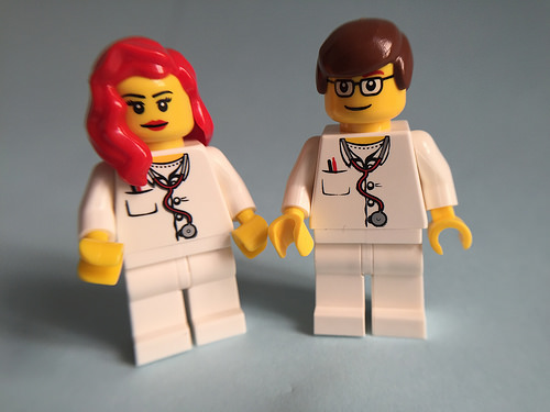2 lego doctors. the one on the left has long red hair. the one of the right has short brown hair and glasses.
