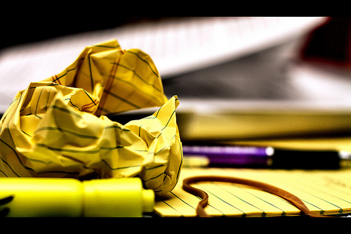 close up photo of a legal pad, a crumpled up piece of paper from the legal pad, a purple pen, a yellow highlighter