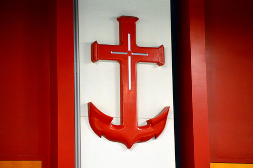a red anchor hanging on a white background with red panels lateral to the white background