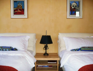 two separate beds with a lamp in the middle and paintings hanging on the wall