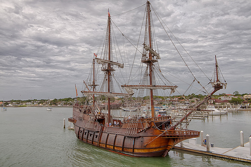 a large galleon (old-fashioned ship with 2 large masts) is docked at a harbor