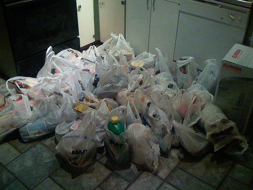 a kitchen floor with a few dozen very full white plastic grocery bags full of groceries sitting on the floor