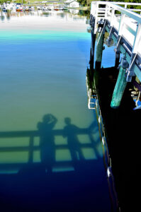 a white pier with a marina. on the water, there is a reflection (a shadow) cast of two people who are standing on the pier (but can't be seen in the image)