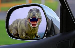 a rearview mirror with a Tyrannosaurus rex in it