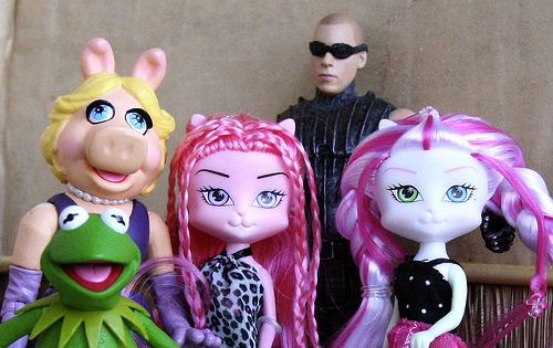 a bunch of metamours: Kermit the Frog, Miss Piggy, a couple of pink cat girls, and a brooding gent in the back with dark shades