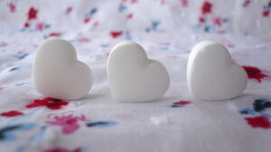 3 white candy hearts on a white background speckled with with fuschia and navy blue dots