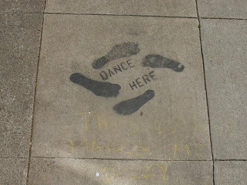 "a concrete block that says ""DANCE HERE"" flanked by 4 footprints"