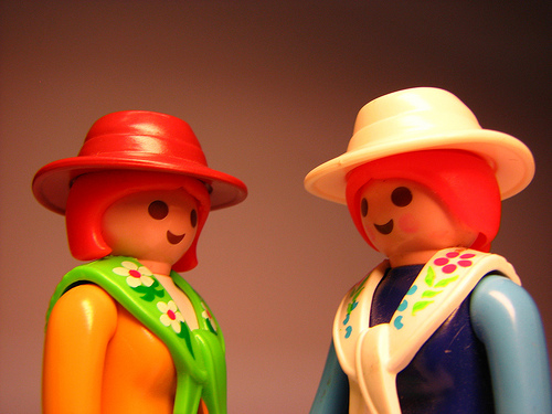 2 plastic toy people who appears to be friends. Both are wearing hats and scarves. They are positioned so that they seem to be in mid-conversation with one another.